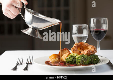 Traditional British roast dinner of rare beef, yorkshire pudding, roast potatoes and brocolli with gravy being poured - Stock Photo