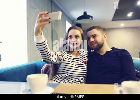 happy young couple with smartphone taking selfie at cafe in mall. sale, shopping, consumerism, technology and people - Stock Photo