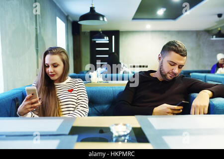 Embracing couple using mobile phone in cafe. Toned. Selective focus. - Stock Photo
