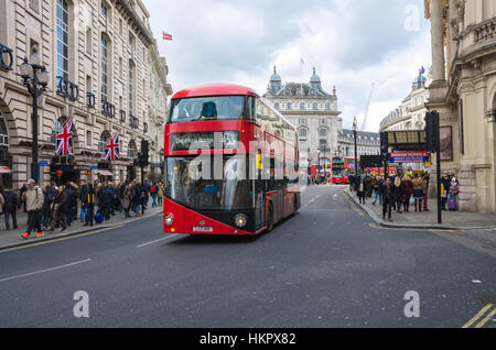 A London double decker bus drives through Piccadilly Circus in London. - Stock Photo