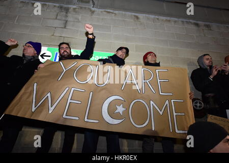 Members of NY City Council stand against wall with banner. Thousands gathered at Terminal Four at JFK Airport to - Stock Photo