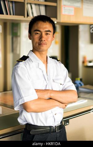 Young Chinese navigator on bridge, navigating his ship at sea. - Stock Photo
