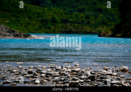 Lake side coast view with mountain background during a bright sunny day - Stock Photo