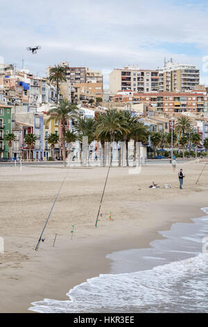 Quadcopter drone flying over a beach in Villajoyosa, Alicante Province, Spain. With fishing poles and fishermen - Stock Photo