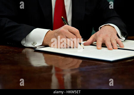 Washington, DC, USA. 30th Jan, 2017. U.S. President Donald Trump signs an executive order in the Oval Office of - Stock Photo
