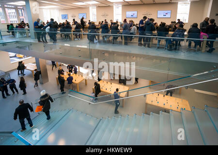 Customers shopping and browsing in the Soho Apple Store in New York City - Stock Photo