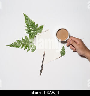 Flat lay of green leaves and flowers pattern with cup of coffee and paper note on white background - Stock Photo