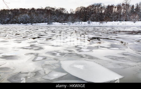 spring season - floating ice floes on surface of river in twilight - Stock Photo