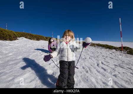 Three years old blonde child with snowball in hand looking ready to throw, next to woman mother, with white and purple coats on snow in winter mountai