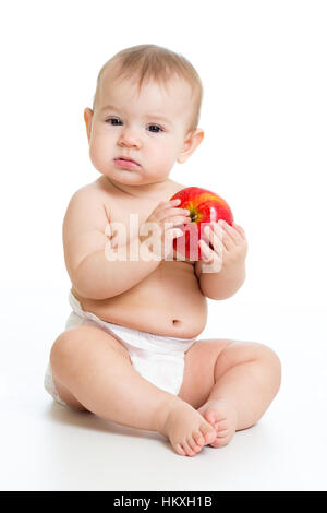 Eight month old baby sitting with apple - Stock Photo