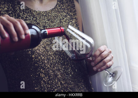 Horizontal close up of Caucasian retro woman in gold sequin vintage dress pouring herself red wine into a tall glass - Stock Photo