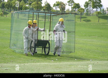 Women in a cage walk over the driving range to collect golf balls, Tomson Golf Club, BMW Asian Open 2004, Shanghai, - Stock Photo
