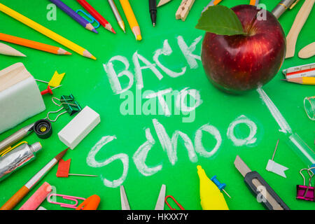 School supplies on Green chalkboard ' Back to school background ' - Stock Photo