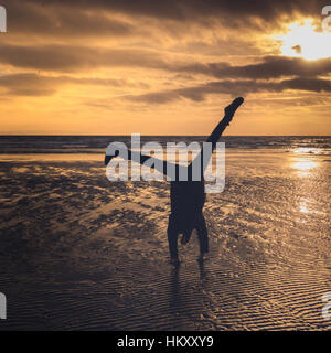 Girl Does A Cartwheel On The Beach At Sunset - Stock Photo