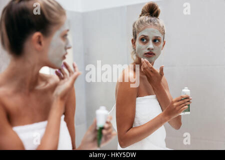 Young woman applying mask cream on face in bathroom. Female in doing beauty treatment on her face skin in front - Stock Photo