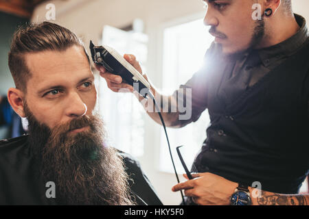 Young man getting haircut at barber shop. Hairstylist cutting hair of client in barber shop. - Stock Photo