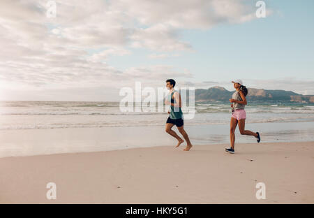 Full length shot of fit young man and woman running on the beach. Couple of runners on the sea shore.
