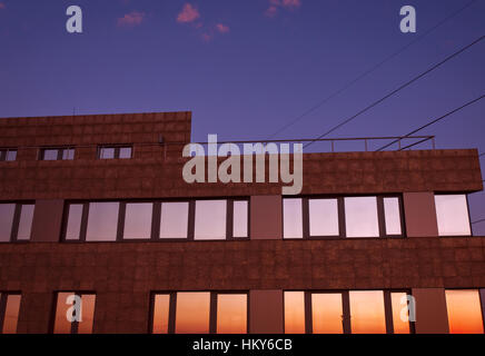 Building at dusk with colorful reflections in the windows against dark violet sky and pink clouds with visible power - Stock Photo