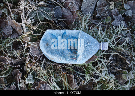 A blue plastic drinks bottle covered in frost on a roadside verge in winter - Stock Photo