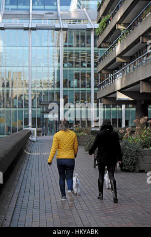 Two women walking dogs outside office buildings at the Barbican in the City of London, UK  KATHY DEWITT - Stock Photo