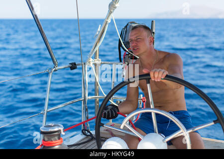 Man skipper at the helm controls of a sailing yacht. - Stock Photo