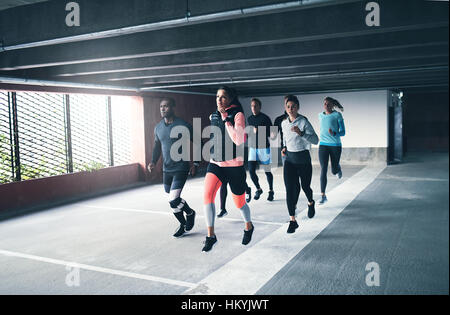 Young team of urban athletes training together running through a covered commercial car park with sun flare through - Stock Photo