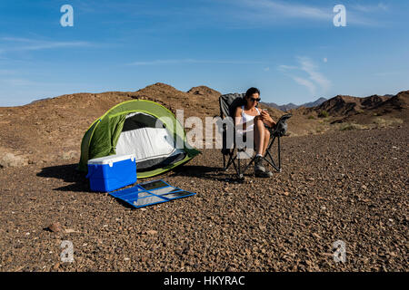 Woman in the mountain playing with her smartphone while it is charging with a foldable solar panel. - Stock Photo
