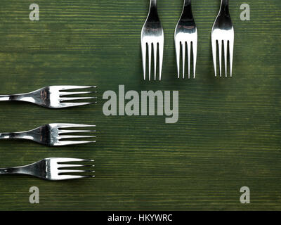 Used Household Kitchen Forks On A Green Board Background - Stock Photo