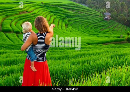 Beautiful view of Balinese fields. Nature walk in green rice terrace. Happy mother hold happy little baby.  Traveling - Stock Photo