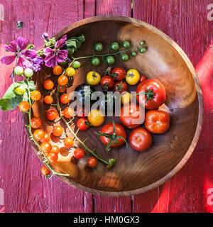 Variety of heirloom tomatoes in a rustic bowl and on a light wood surface - Stock Photo