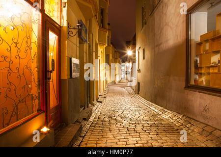TALLINN, ESTONIA - 20 DEC 2015. Old town narrow street at night. Bright stoned road and lantern. - Stock Photo