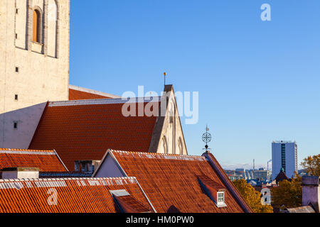 Red roofs of St. Nicholas Church (Niguliste) and close houses at sunny summer day - Stock Photo