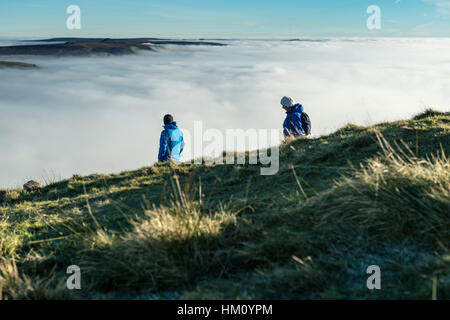 Male and female hikers descend from the peak of Mam Tor, Peak District, Hope Valley on a cold winter morning - Stock Photo