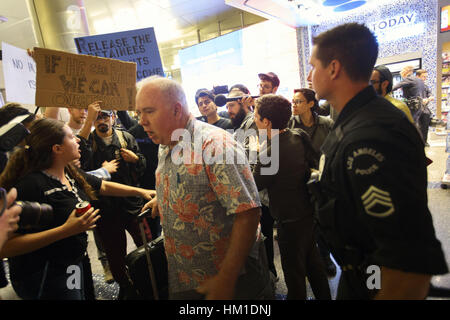 Los Angeles, USA. 29th Jan, 2017. A traveler disagreeing with protesters is confronted inside of the arrivals level - Stock Photo