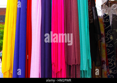 Yellow, purple, red, baby pink, dark, fluo pink, brown and green scarves on display at a street market in London. - Stock Photo