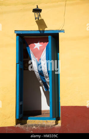 Cuban flag hanging in a colorful doorway in old Trinidad, Cuba - Stock Photo