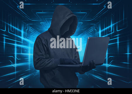 Hacker man with mask using laptop while standing against digital background - Stock Photo