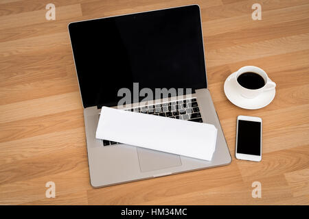 laptop with coffee cup  and smart phone,newspaper on wood table - Stock Photo