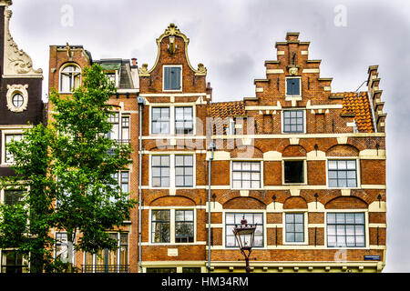 Gable of Historic Houses along the Canals in the Old City Center of Amsterdam in the Netherlands - Stock Photo