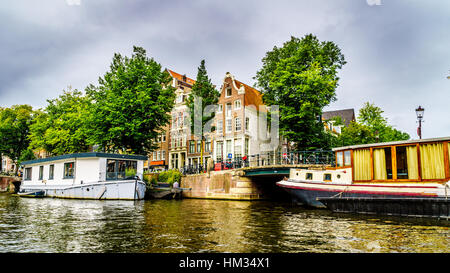 Historic Buildings with Ornate Gables along the canals in old city of Amsterdam in the Netherlands - Stock Photo