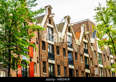 Spout Gables of Historic Houses along the Canals in the Old City Center of Amsterdam in the Netherlands - Stock Photo