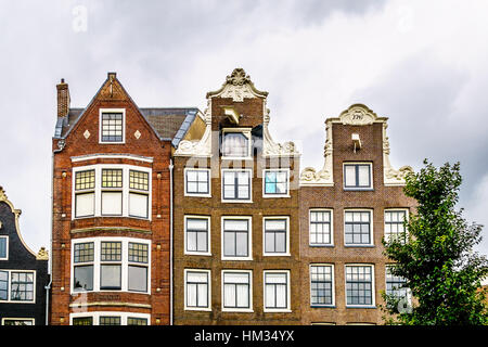 Spout and Bell Gables of Historic Houses along the Canals in the Old City Center of Amsterdam in the Netherlands - Stock Photo
