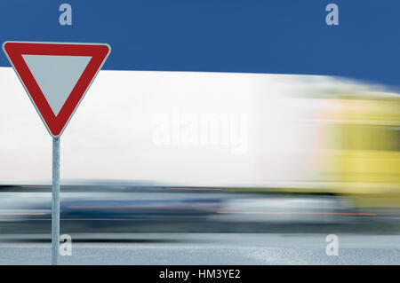 Give way yield road traffic sign and motion blurred truck lorry in the background - Stock Photo