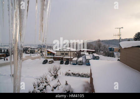 icicles built up outside a window overnight in Furano, Hokkaido, Japan - Stock Photo