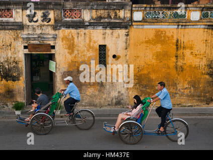 Cyclo drivers and yellow walls in the picturesque old town of Hoi An, Vietnam - Stock Photo