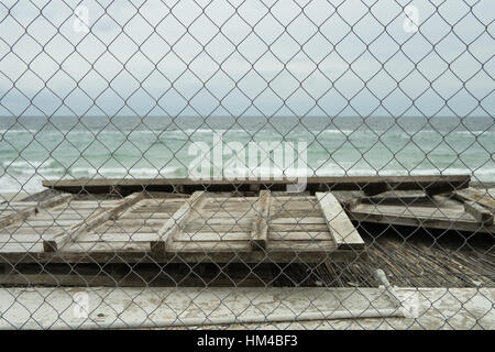 In the foreground is part of wooden buildings, in the background the sea on a cloudy day. Look through the netting. - Stock Photo