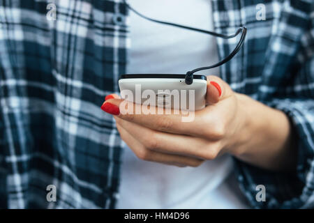 Girl in plaid shirt holding a smart phone in her hand with red manicure - Stock Photo