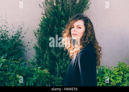 Young Caucasian woman with curly hair in a black jacket walks down the street in the sunlight - Stock Photo