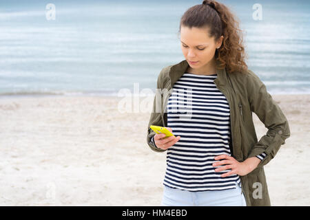 Young girl in a green jacket uses yellow mobile phone on the beach - Stock Photo
