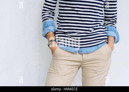 Close-up of a woman in a denim shirt, striped t-shirt and beige pants with a fitness tracker at hand, the details - Stock Photo